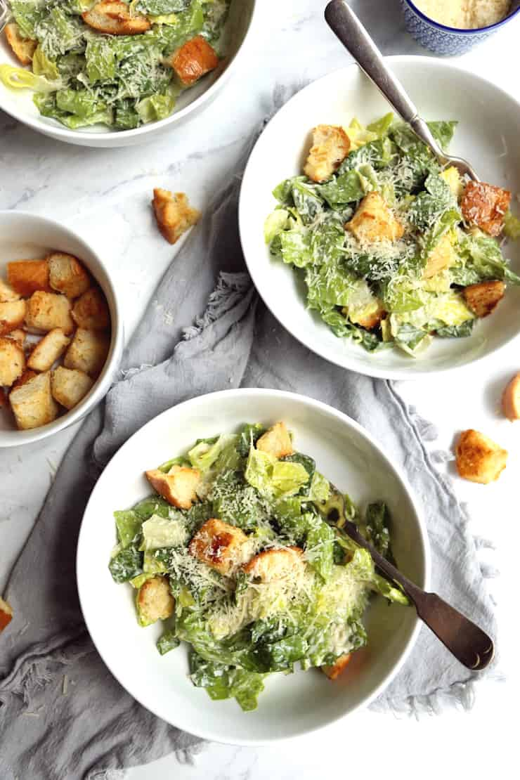 overhead view of Classic Caesar Salad with garlicky sourdough croutons in white bowls on marble background