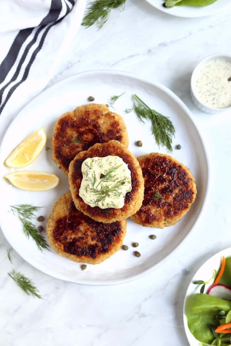 overhead image of 4 salmon burgers on white plate with tartar sauce and lemon wedges