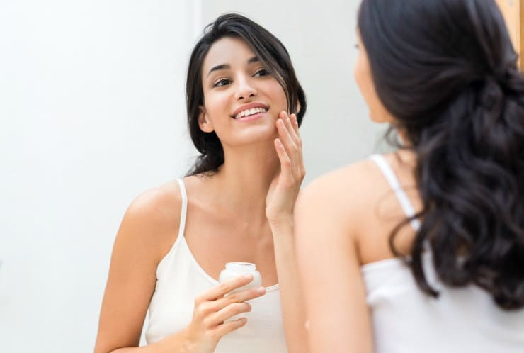 woman applying natural skin cream in mirror