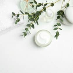 overhead image of natural face cream and white towel on white background