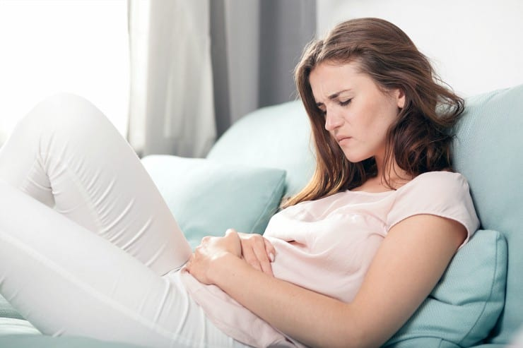 Young woman with stomach pain lying on the couch