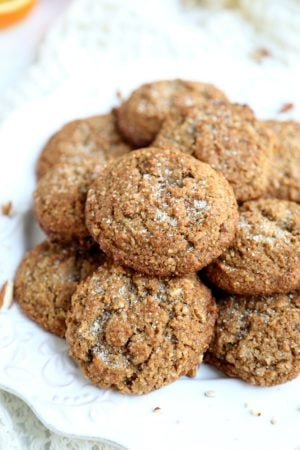 Close up view of pile of pecan flour spice cookies on white plate