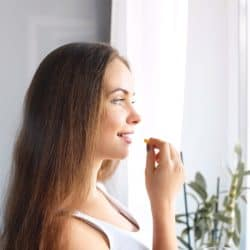 Happy young woman looking out apartment window, taking dietary supplements