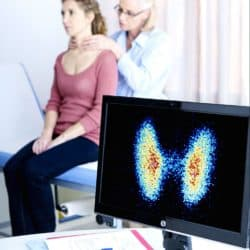 Image of doctor examining a woman's thyroid