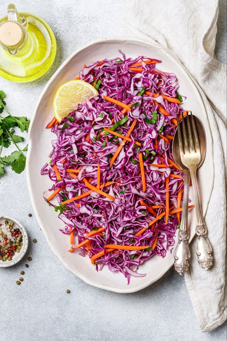 overhead image of purple calbbage and carrot slaw on light gray background