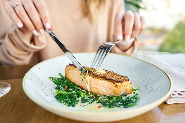 close up of woman cutting into salmon steak on a bed of spinach
