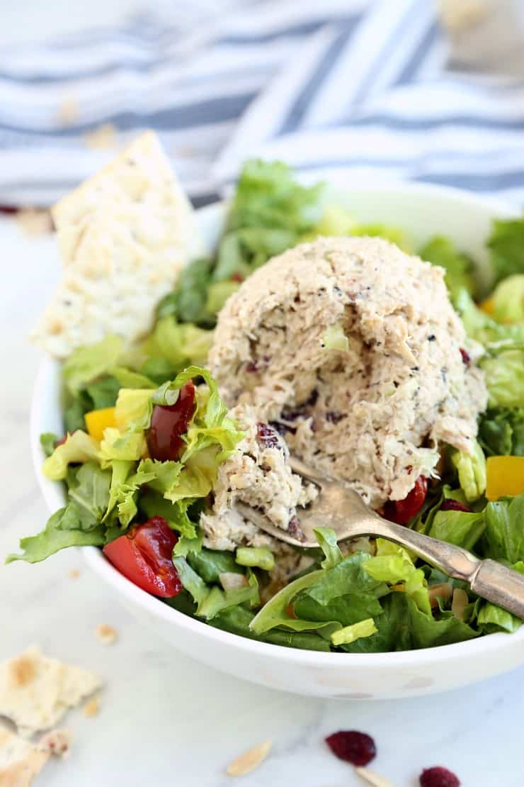 Close up image of Magic Everything Tuna Salad on a bed of greens with a bite on a fork.