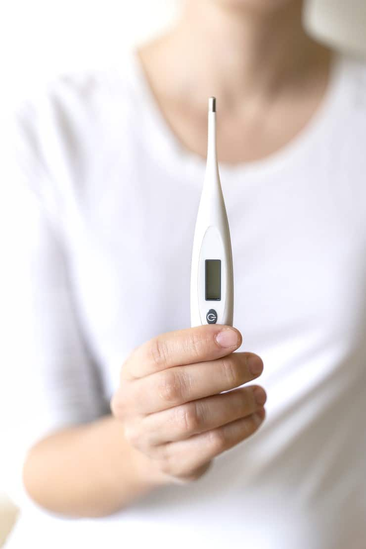 Close up image of woman holding digital thermometer