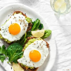 overhead view of 2 fried eggs on avocado toast with wilted greens. white plate on white background.