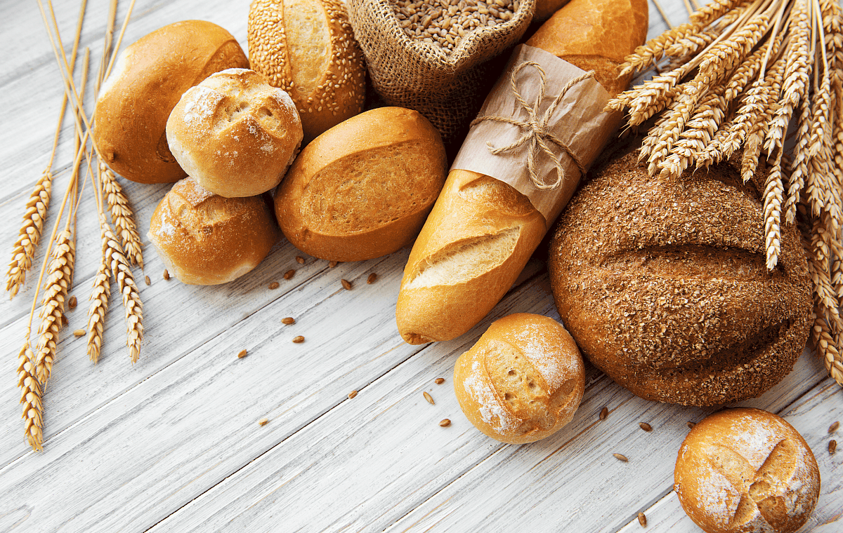 overhead image of various gluten containing breads on a white wood background
