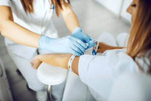 Phlebotomist preparing to draw blood from woman's arm