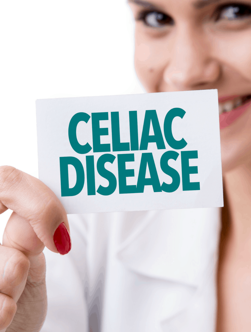 smiling female doctor in lab coat holding Celiac Disease sign