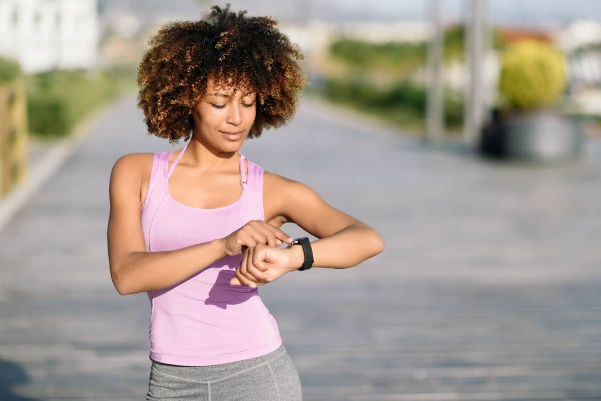 Black woman out jogging on city street, stopped to check her time