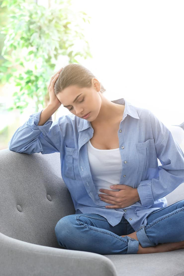Brunette woman sitting on gray couch holding her stomach in pain