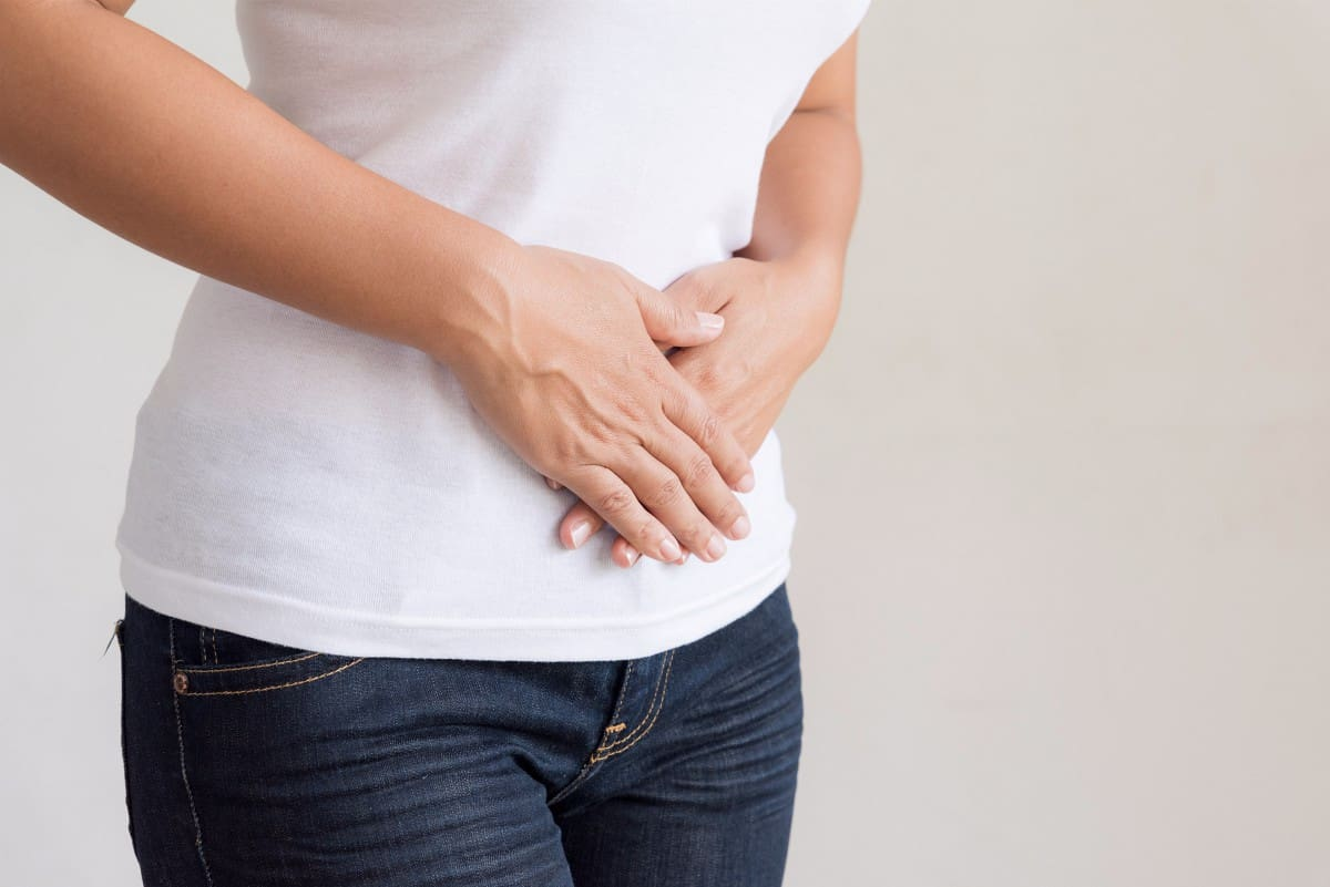 close up image of woman holding her stomach in pain