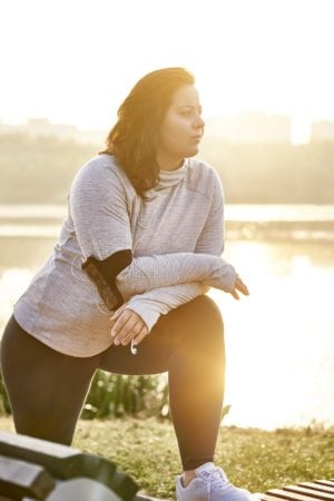 Brunette woman stretching on bench in middle of her morning run