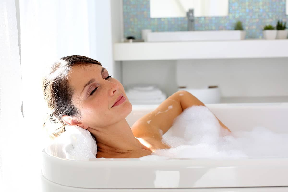 Brunette woman relaxing with her eyes closed in a bubble bath in a white tub.