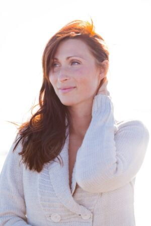 Peaceful red headed woman in white sweater outside gazing off into the distance