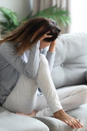 Young brunette woman on gray couch feeling anxious with head in her hands