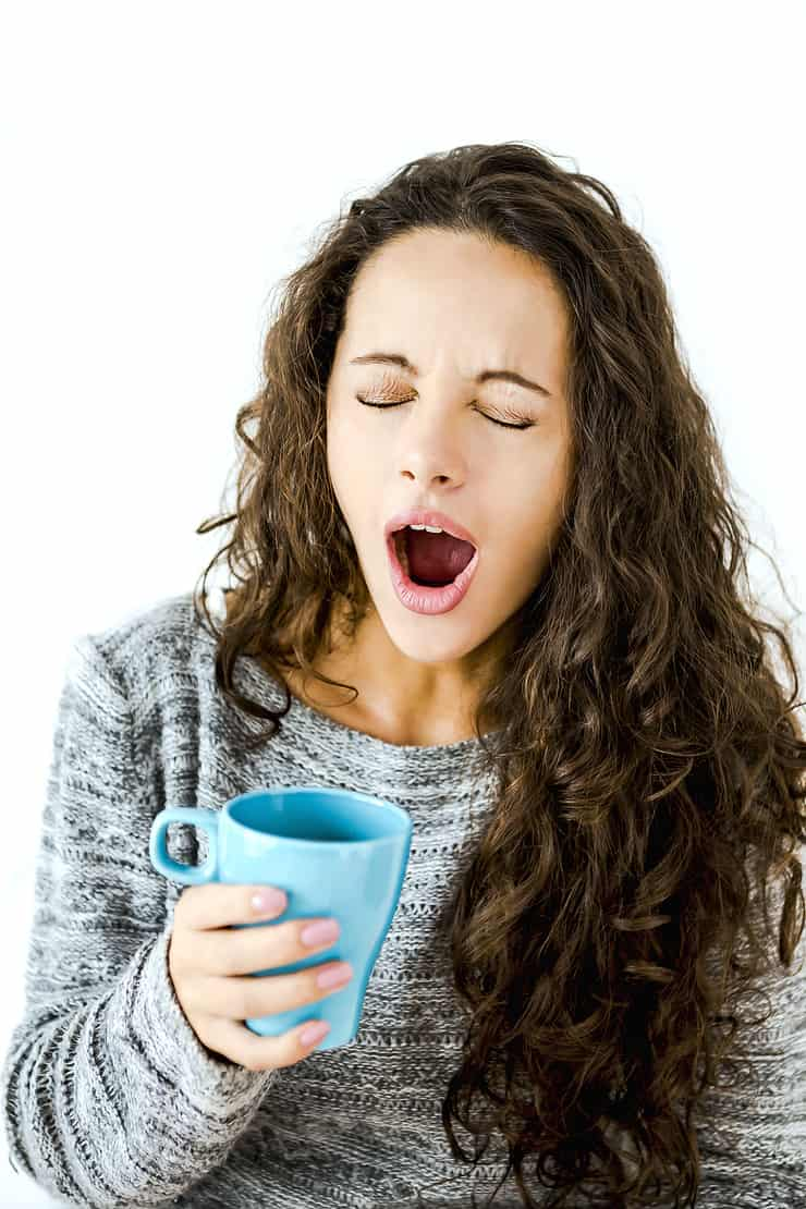 Woman yawning while drinking a cup of coffee