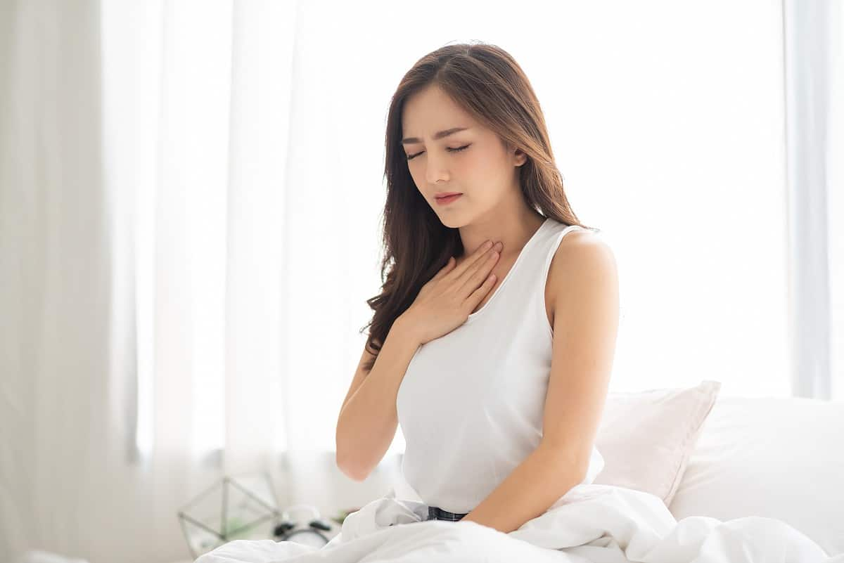 Young Asian woman holding a hand to hear throat in pain from heartburn