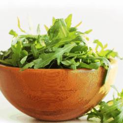 close up image of wooden bowl of arugula leaves on white background