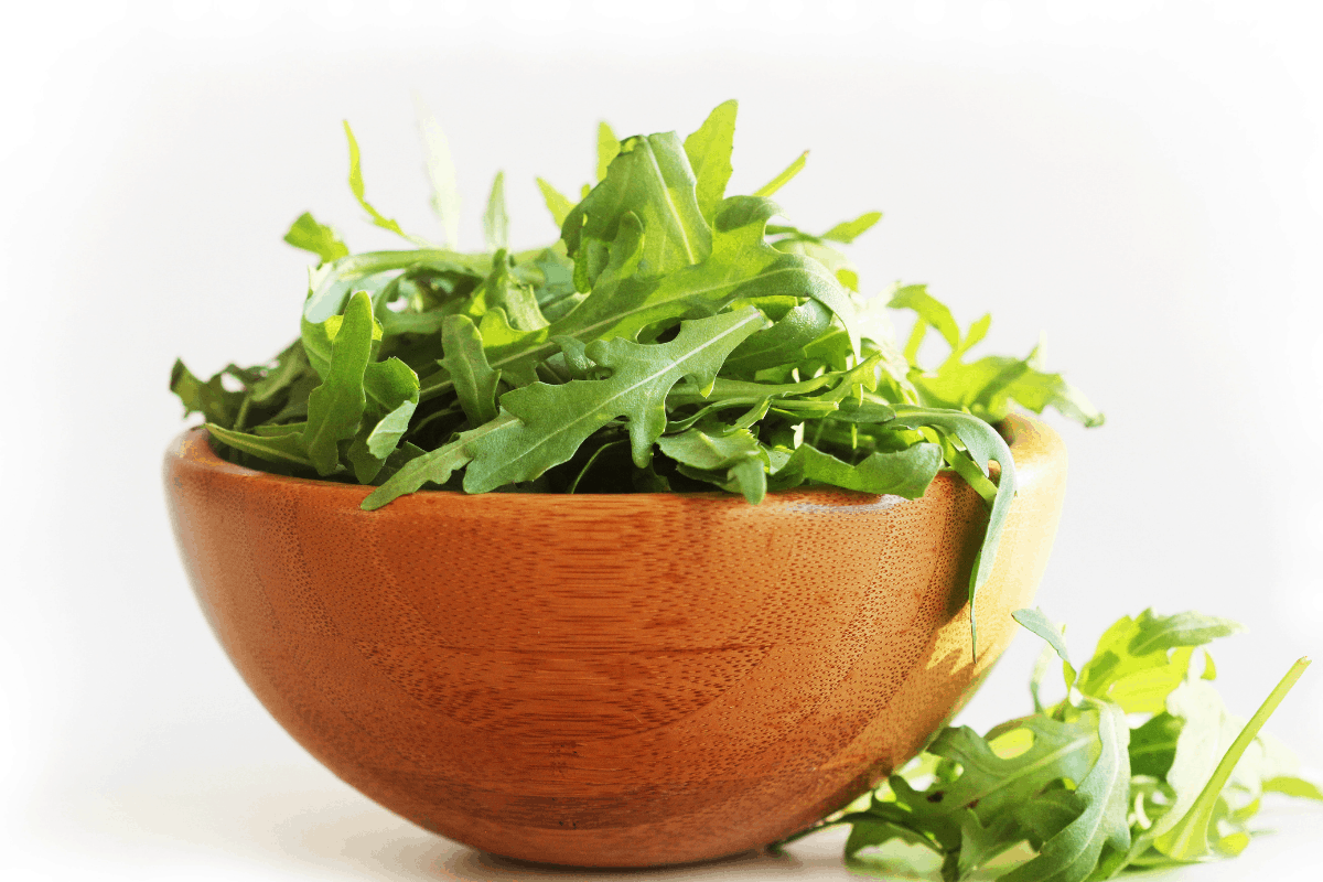close up image of wooden bowl of arugula leaves to help raise stomach acid