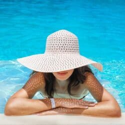 tan woman in pool, leaning arms on edge and wearing a straw sun hat