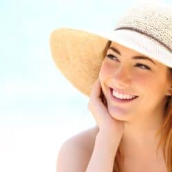 Beautiful brunette woman with sun hat smiling on the beach