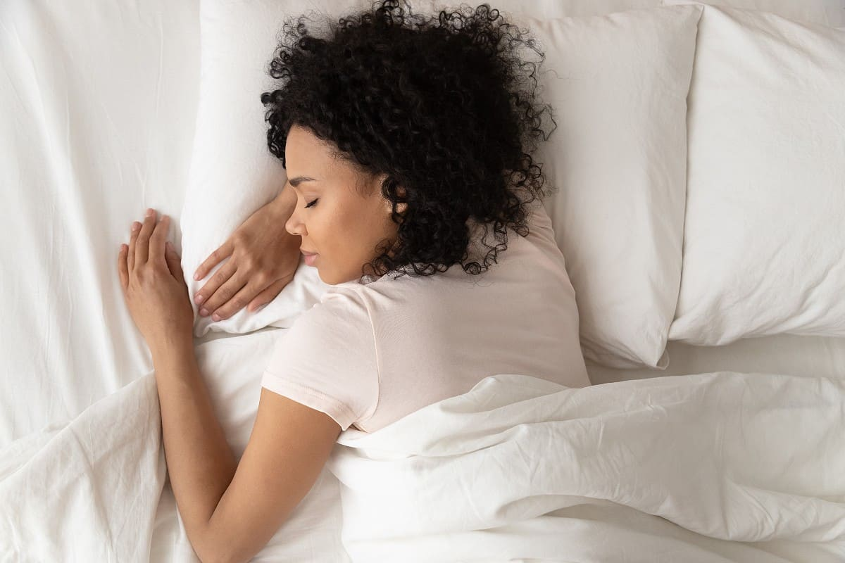 African American woman sleeping peacefully in bed with white bedding