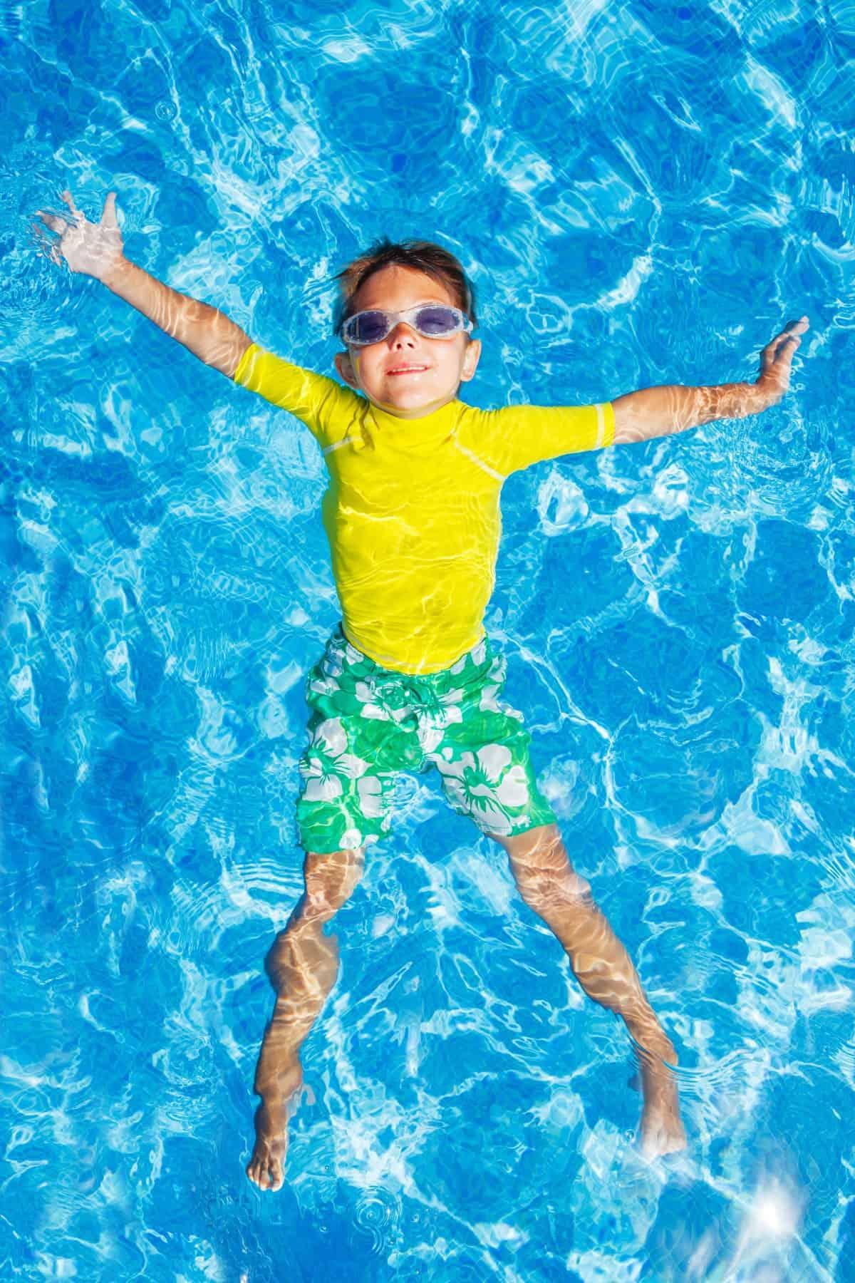 Overhead view of young boy swimming in pool wearing sun protective rash guard