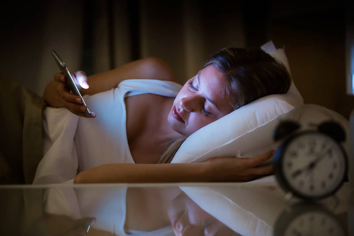 Woman lying in bed with insomnia scrolling her phone