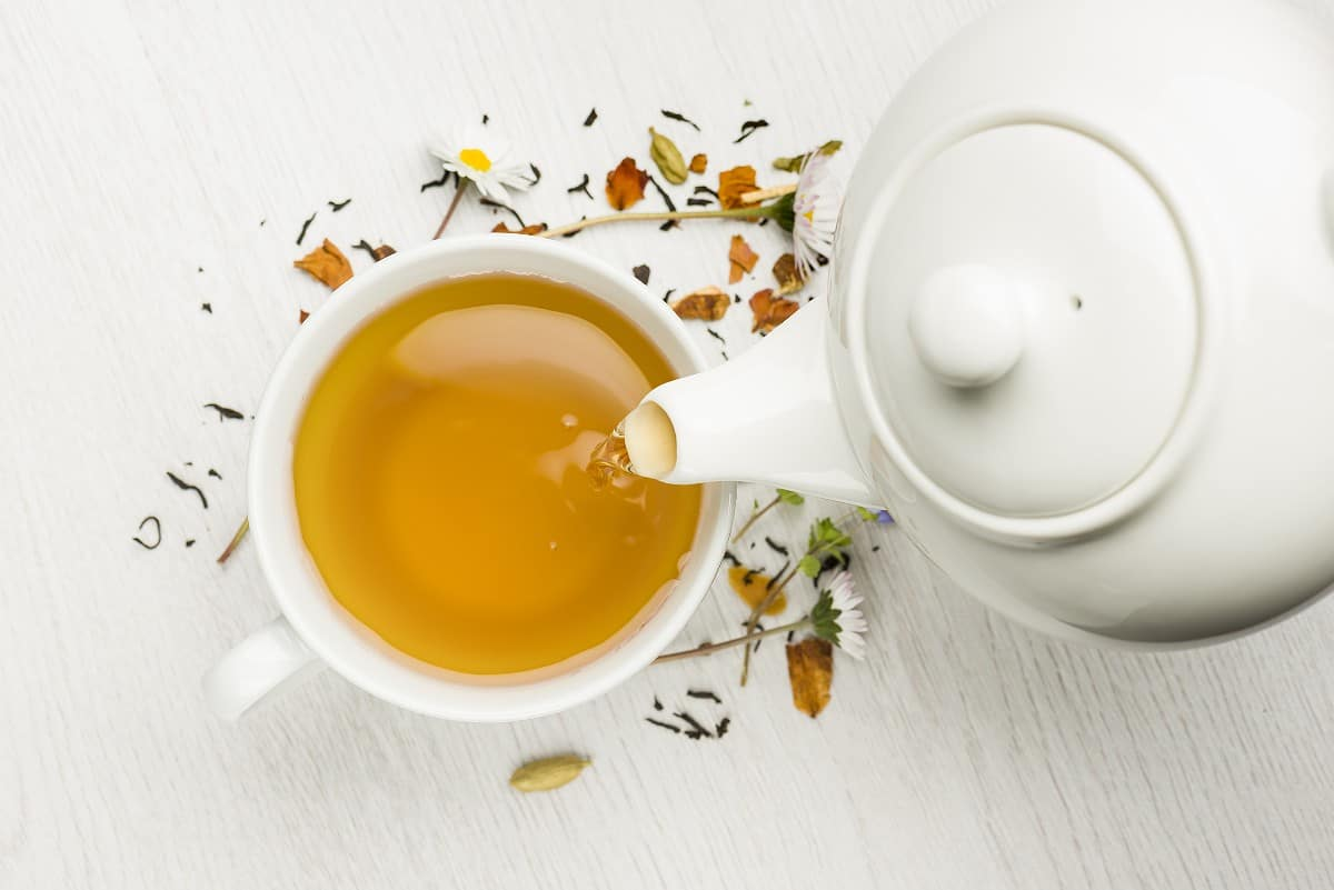 overhead view of white teapot pouring herbal tea into teacup on white background with chamomile and other herbs sprinkled around