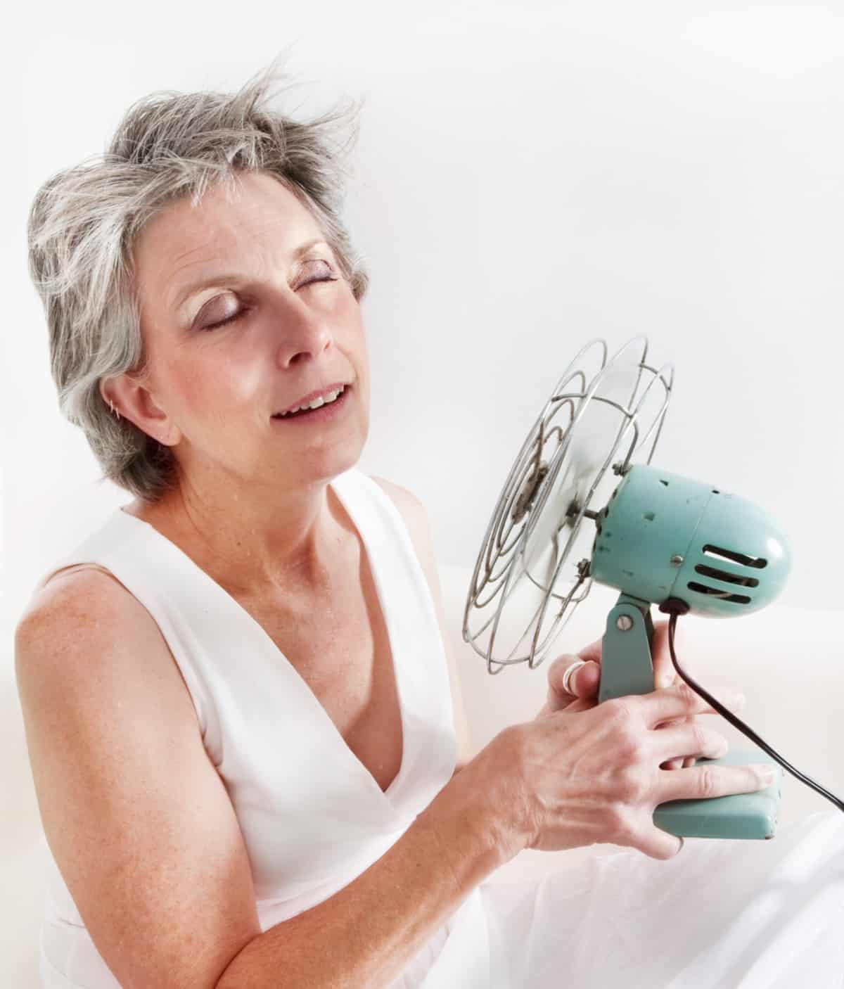 Menopausal woman using fan to cool down during a hot flash