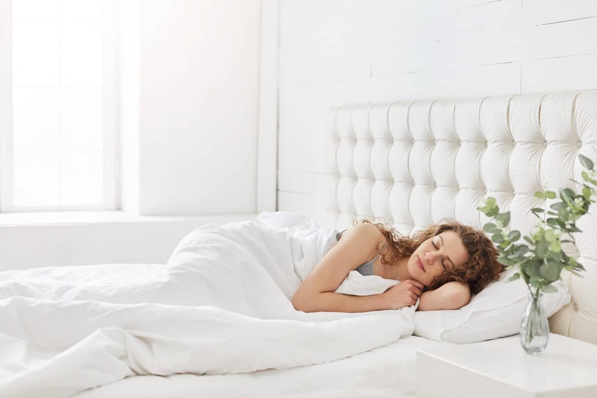red headed woman sleeping soundly in bed with cozy white comforter