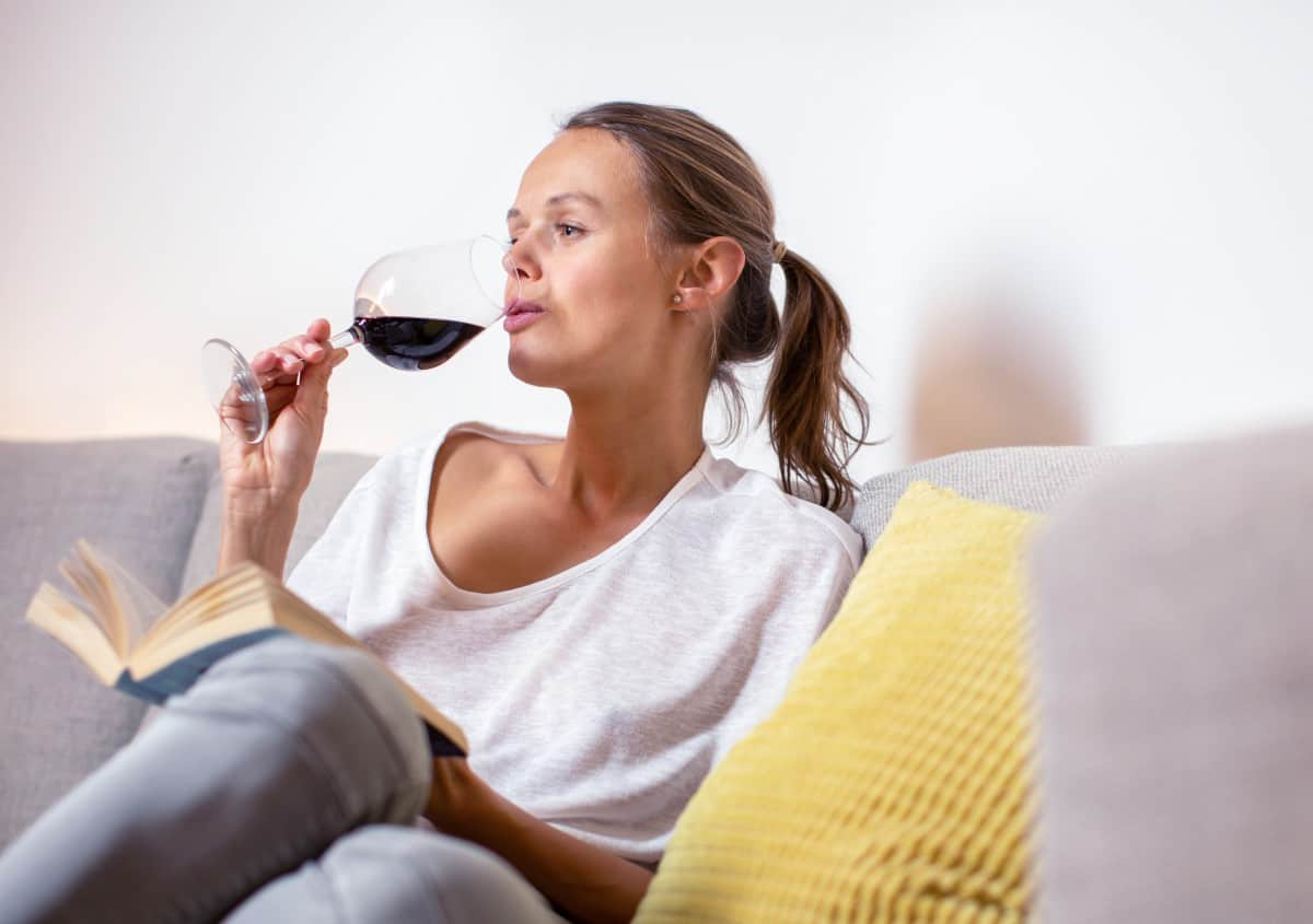 Woman in her 30 curled up on couch enjoying a book and glass of red wine