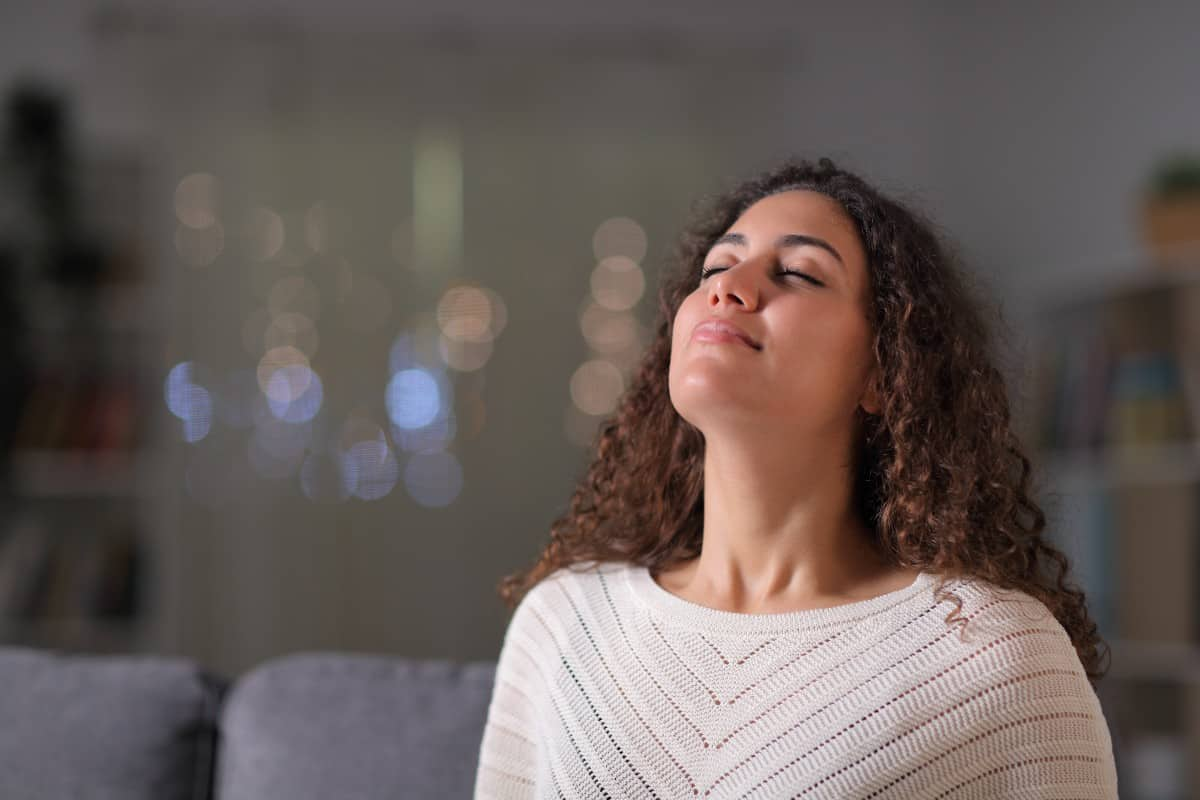 woman practicing deep breathing in evening for better sleep