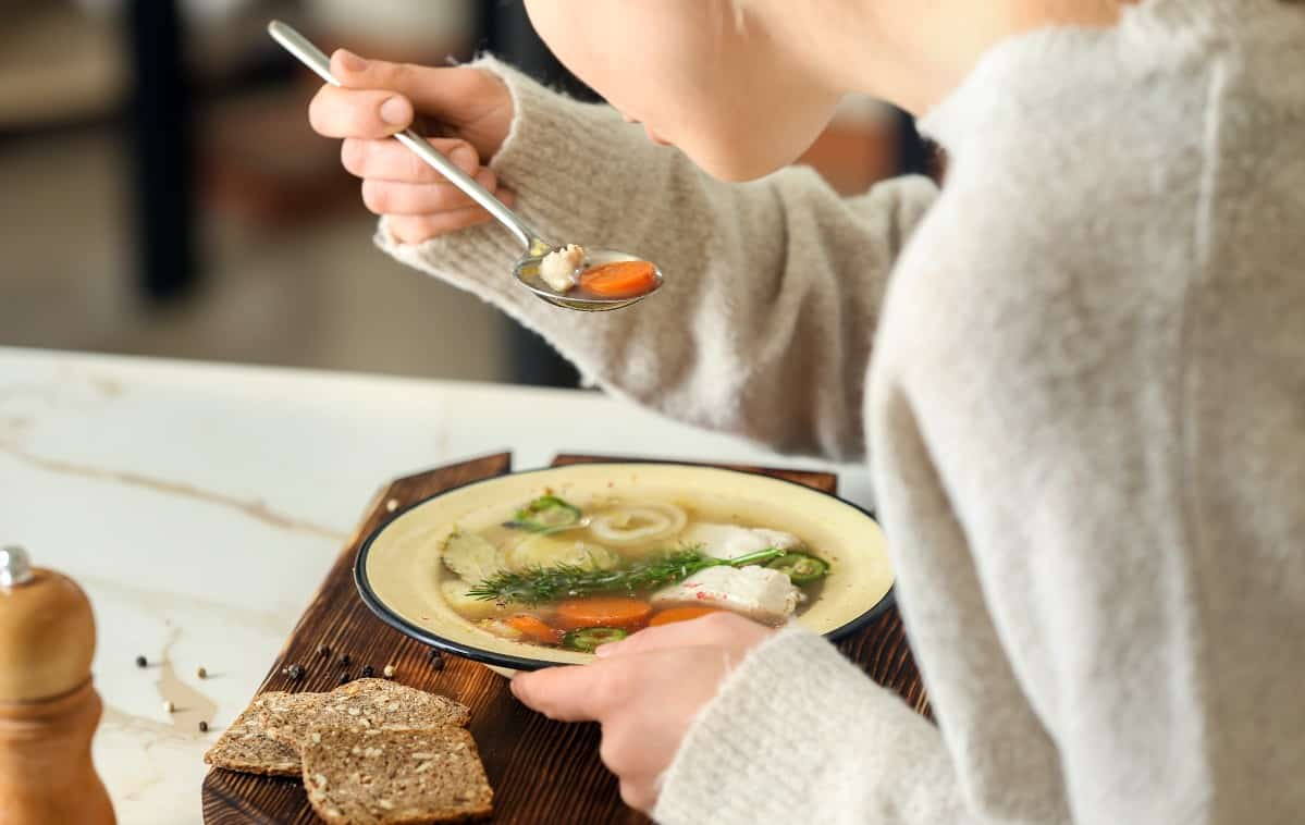 Close up of woman eating bowl of homemade fish soup with vegetables in broth